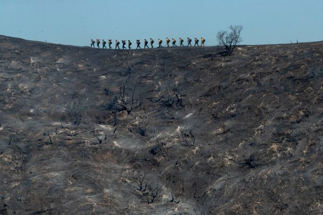 Fire crews walk along a blackened ridge as they battle the Getty fire Monday in Los