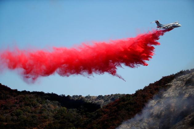 A plane drops fire retardant as the Getty fire burns Monday in Los Angeles' Mandeville