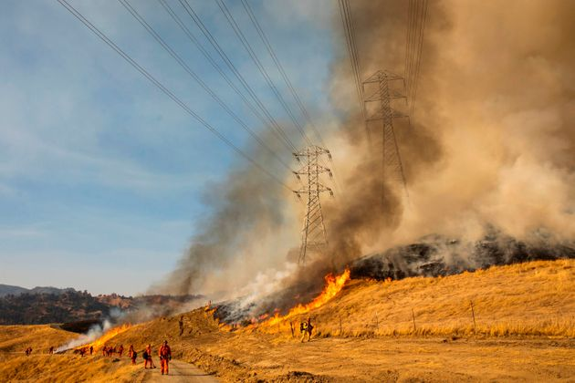 A back fire burns a hillside near PG&E power lines during firefighting operations to battle the Kincade...