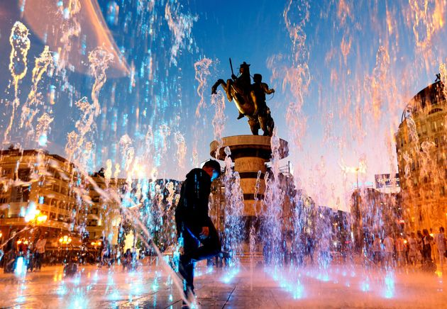 People play with water from a fountain near the