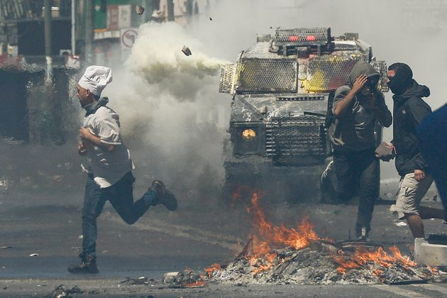 A man wearing a chef's hat runs for cover as anti-government protesters clash with police in Valparaiso,...