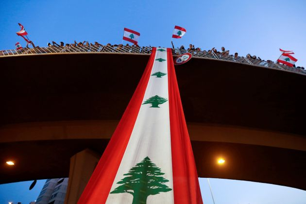 Demonstrators stand on a bridge decorated with a national flag during an anti-government protest along...