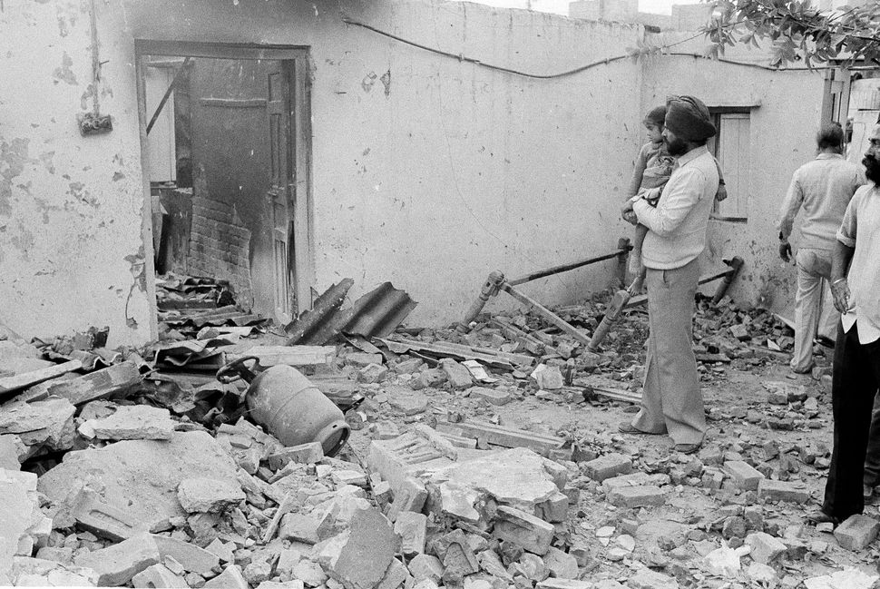 A Sikh man looks at the smashed door and the rubble in front of his house in New Delhi, 2 November, 1984.