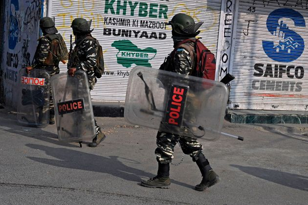 Security forces walk across a street during a lockdown in Srinagar on October 29,