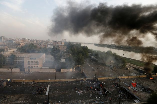 Smoke rises over Baghdad, during a protest over corruption, lack of jobs, and poor services, in Baghdad,...