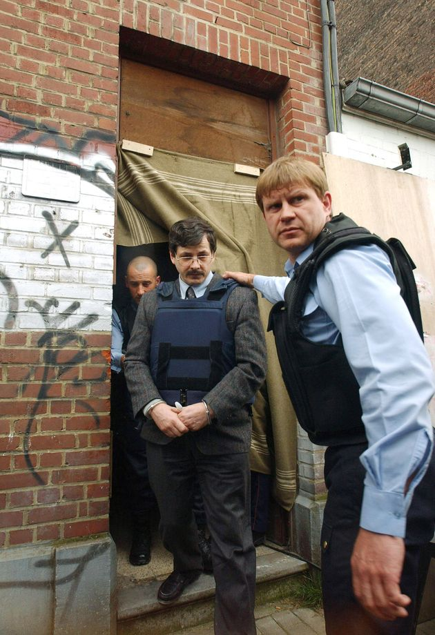 Child rapist Marc Dutroux (C) leaves his house, where he kept his victims locked up, during a visit by...