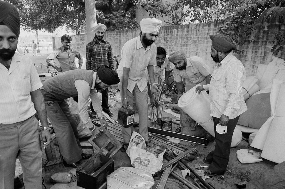 Members of the Sikh community, whose house were attacked, burned and looted, are seen as they collect their looted property in a Delhi police station, 6 November, 1984.