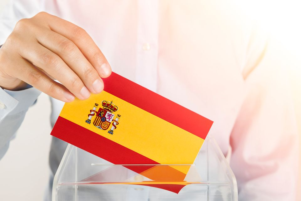 Human hand is inserting Spain flag into ballot box.