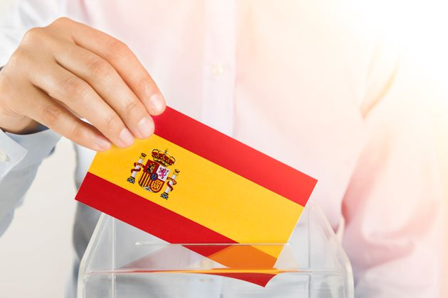 Human hand is inserting Spain flag into ballot
