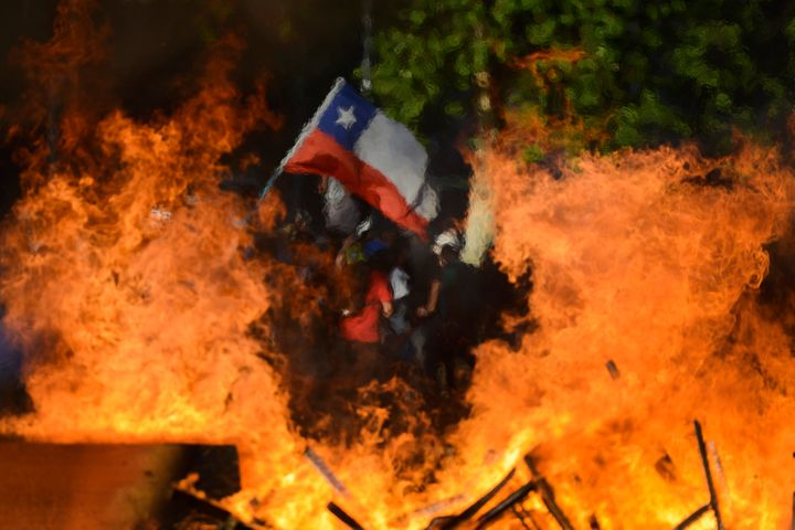 Seen through a burning street barricade, an anti-government demonstrator waves a Chilean flag in Santiago, Chile, on Oct. 28,