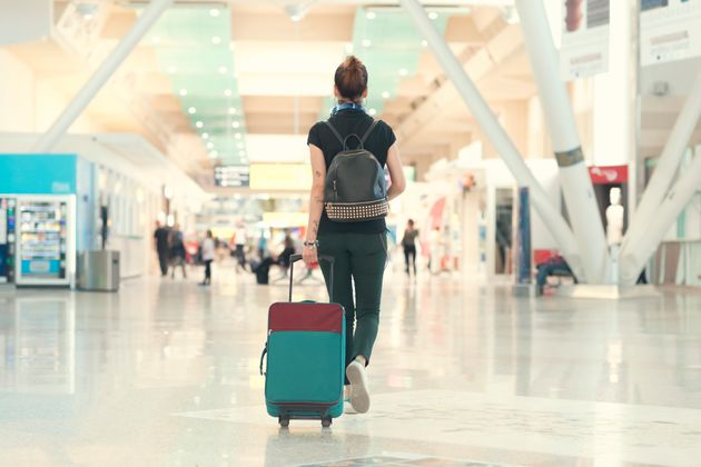 Back view of woman pulling her luggage strolling inside the airport