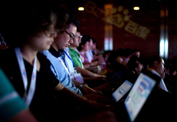 Convention participants use their laptops during a technology innovation conference held by Baidu Inc., which operates China's dominant search engine.