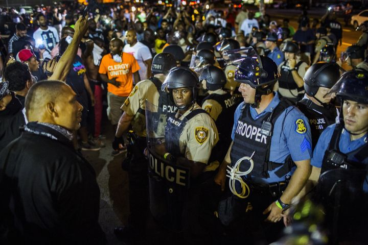 St Louis County police officers interact with anti-police demonstrators during protests in Ferguson, Missouri in August 2015.