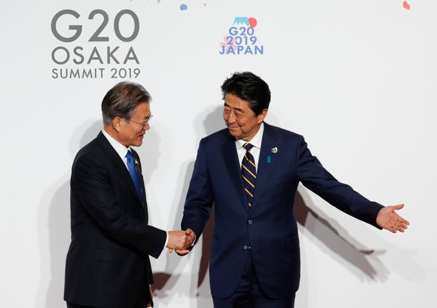 South Korean President Moon Jae-in, left, is welcomed by Japanese Prime Minister Shinzo Abe upon his...