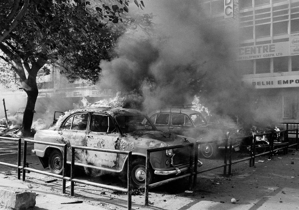 A fleet of Sikh owned cars burn and are covered in thick black smoke after they were set on fire in New Delhi, 1 November, 1984.