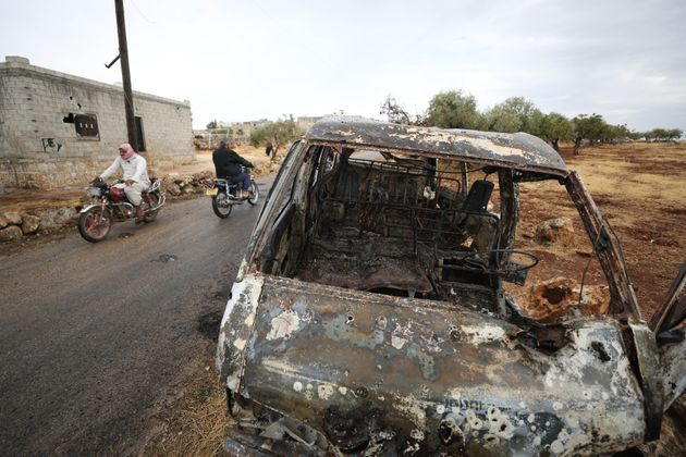 A picture taken on October 28, 2019 shows Syrian bikers riding past a damaged car at the site of a suspected...