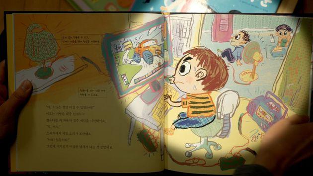 유아용 동화책에 성역할 고정관념이 드러난 장면. 아이 뒤로 아빠는 등을 젖히고 앉아 선풍기 바람을 쐬며 쉬고 있고 엄마는 집안일을 하고