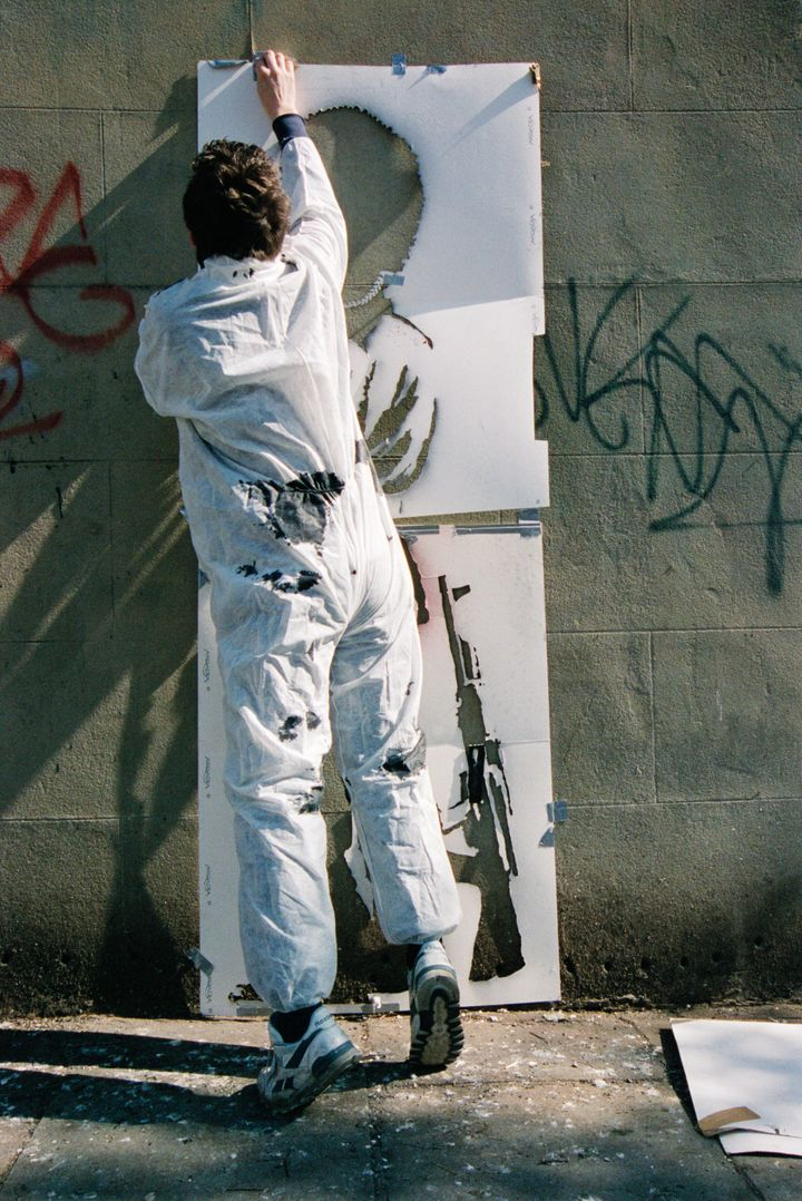 "Banksy, pictured by Lazarides, putting up his ""Pissing Guard"" piece."