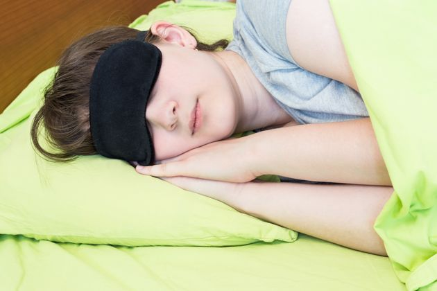 girl teenager in black mask sleeps on green