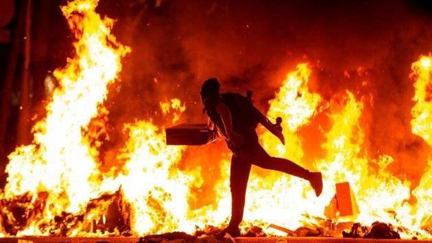 Un manifestante echa al fuego un cartón junto a la Delegación del Gobierno en Barcelona durante los