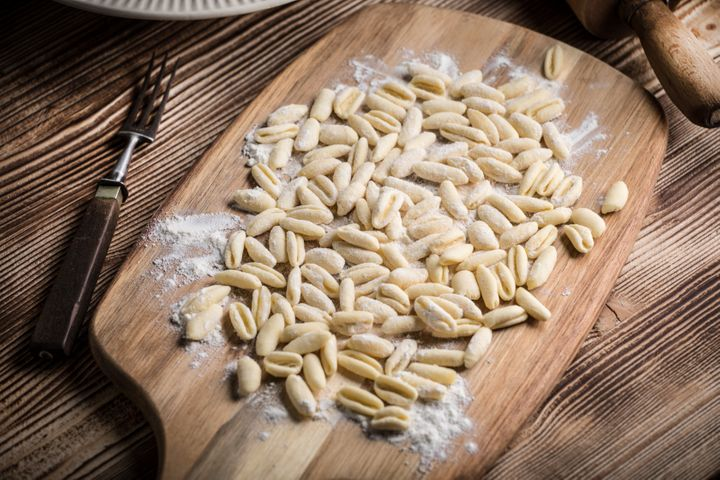 Cavatelli pasta on wooden cutting board.