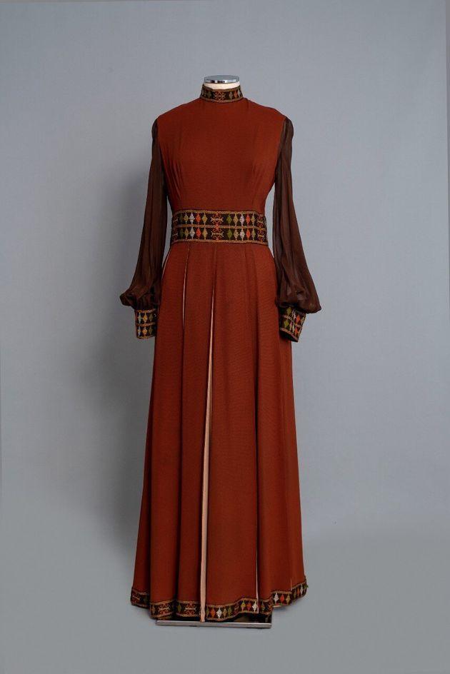 1970-36. Φόρεμα μάξι από καφέ κρεπ με ενυφασμένα γεωμετρικά σχέδια του οίκου «Nikos-Takis». Δεκαετία 1970. Δωρεά: Νένα Σακελλαροπούλου