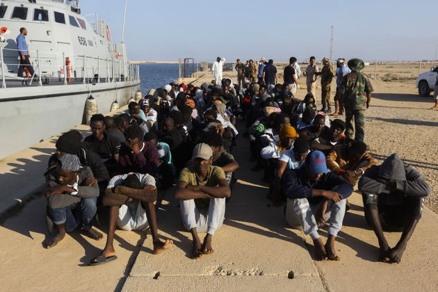 Rescued migrants are seated next to a coast guard boat in the city of Khoms, around 120 kilometers (75...