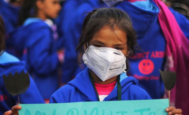 File photo of a schoolgirl with a mask to fight pollution and participate in a demonstration to demand...