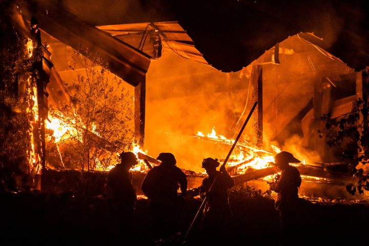 Firefighters tend to a structure lost during the Kincade fire in Healdsburg on Tuesday night.