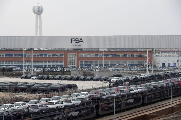Cars are pictured parked in a lot in front of the French automaker PSA Peugeot-Citroen Poissy plant on...