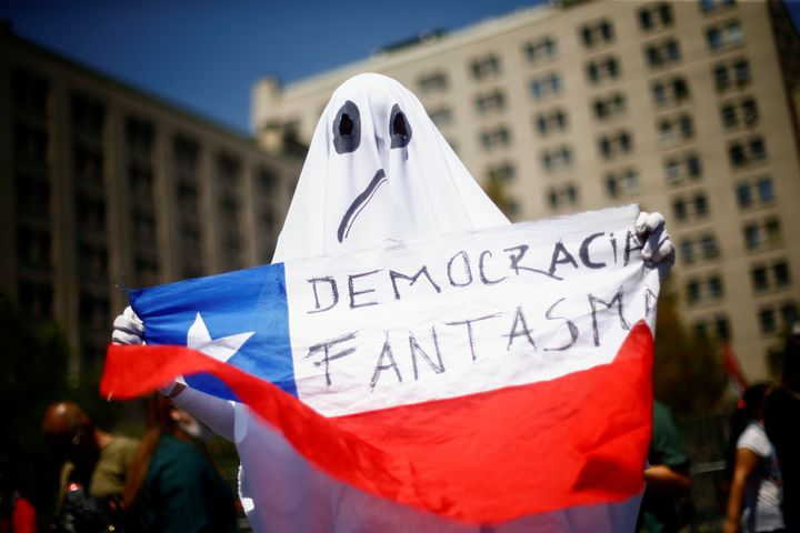 "A demonstrator dressed as a ghost holds a Chilean flag with the legend ""ghost democracy"" during anti-government protests in S"