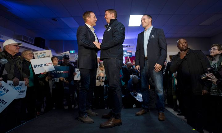 Local conservative candidate George Canyon, right, looks on as Conservative leader Andrew Scheer, centre, shakes hands with Peter MacKay during a campaign stop in Little Harbour, N.S. on Oct. 17, 2019.