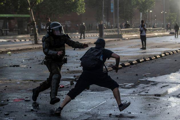 Un antidisturbios trata de atrapar a un manifestante durante los disturbios en