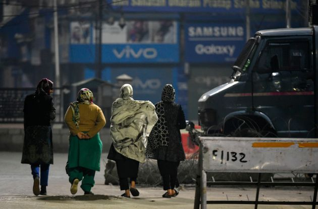 Kashmiri women walks near an paramilitary armoured vehicle during a lockdown in Srinagar on October 30,...