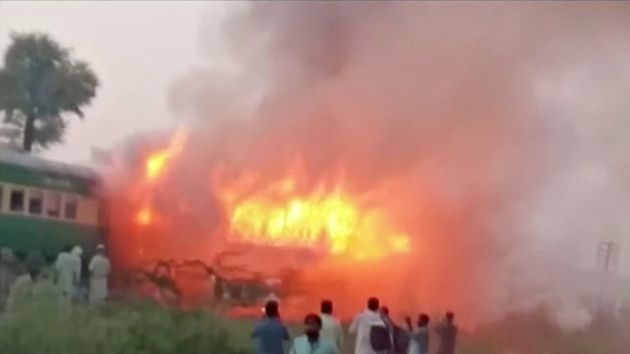People watch fire burning a train after a gas canister passengers were using to cook breakfast exploded,...