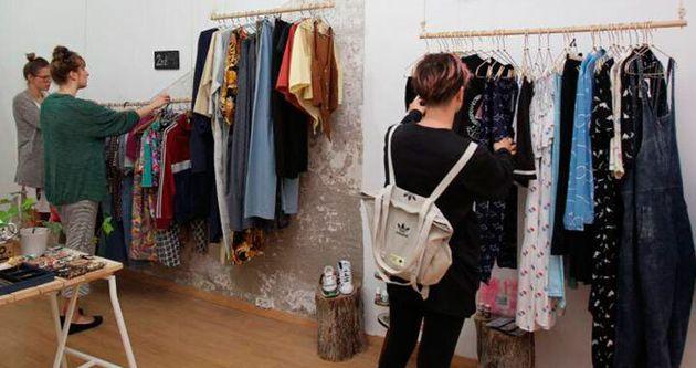 Tres clientas examinan la ropa de una tienda de