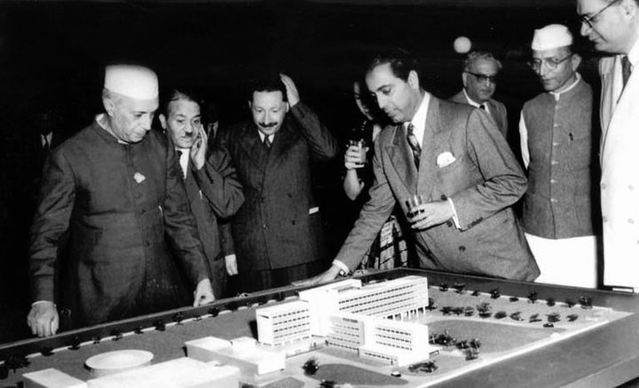 Homi Bhabha (glass in one hand and other on the table) showing Prime Minister Nehru the model of the Tata Institute of Fundamental Research (TIFR).