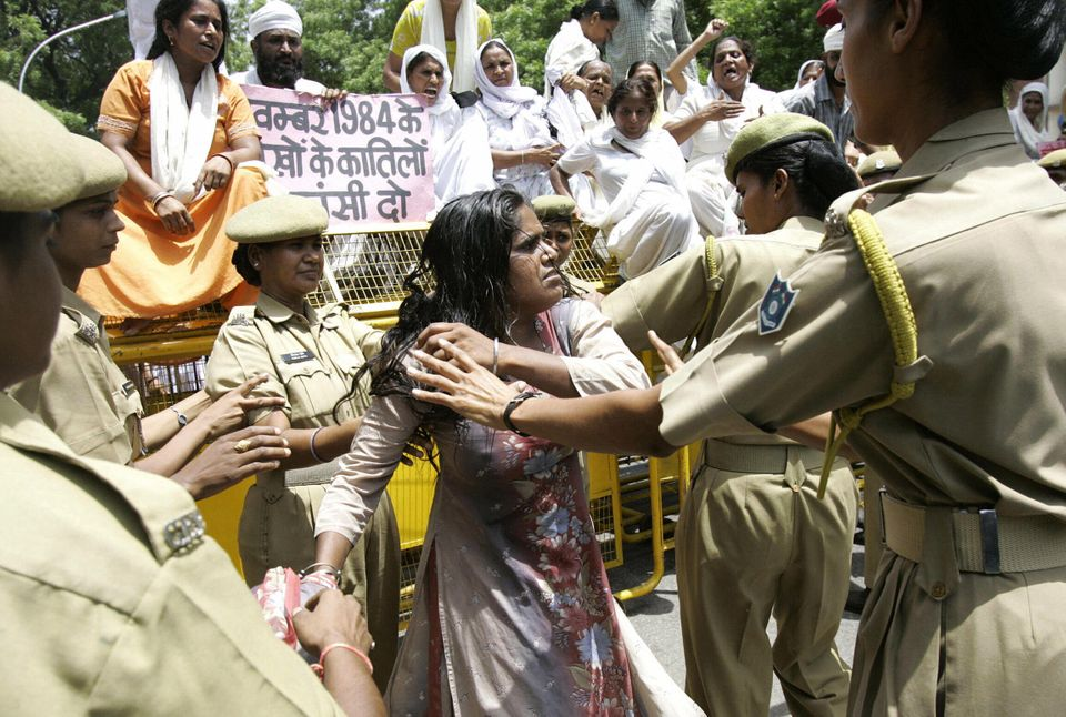 Police women tussle with widows and relatives of Sikh men who were killed in the 1984 pogrom during a...