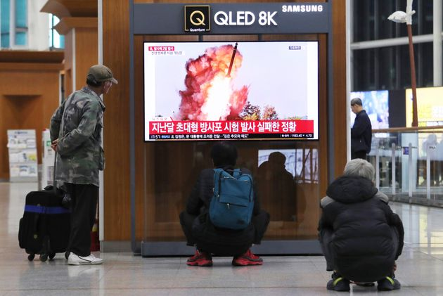 People watch a TV showing a file image of an unspecified North Korea's missile launch during a news program...