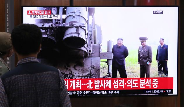 People watch a TV showing a file image of North Korean leader Kim Jong Un during a news program at the...