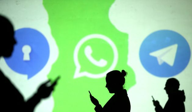 Silhouettes of mobile users are seen next to logos of social media apps Signal, Whatsapp and Telegram....