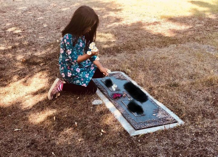 Leah Campbell's daughter arranging flowers at the grave they chosen to represent the father she never met.