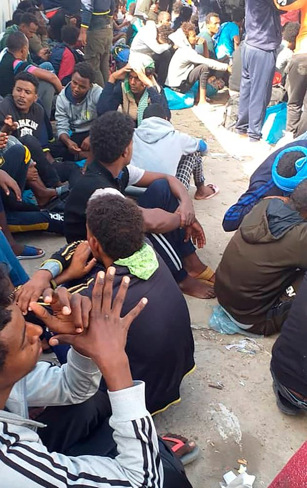 Hundreds of migrants who fled a detention center in coastal Libya crowd around a U.N. facility in Tripoli,...