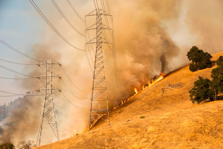 Firefighters battle flames behind PG&E power lines in Healdsburg, California, on Oct. 26.