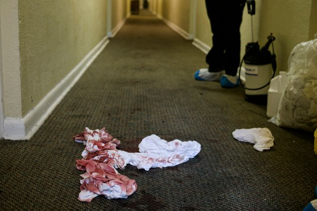 A cleaning crew works to remove blood from the carpet of a building where a shooting took place the night...