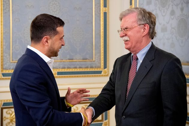 Ukrainian President Volodymyr Zelenskiy shakes hands with U.S. National Security Advisor John Bolton...