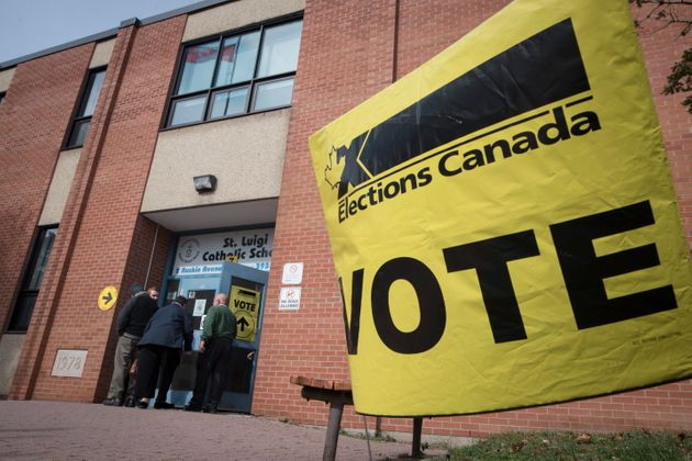 Voters enter the polling station at St. Luigi Catholic School during election day in Toronto on Oct....