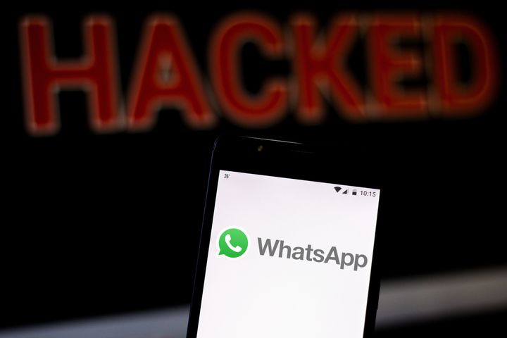 In this photo illustration, the WhatsApp logo is seen displayed on a smartphone and red alerting word HACKED on the blurred background. Conceptual photo for data breach.