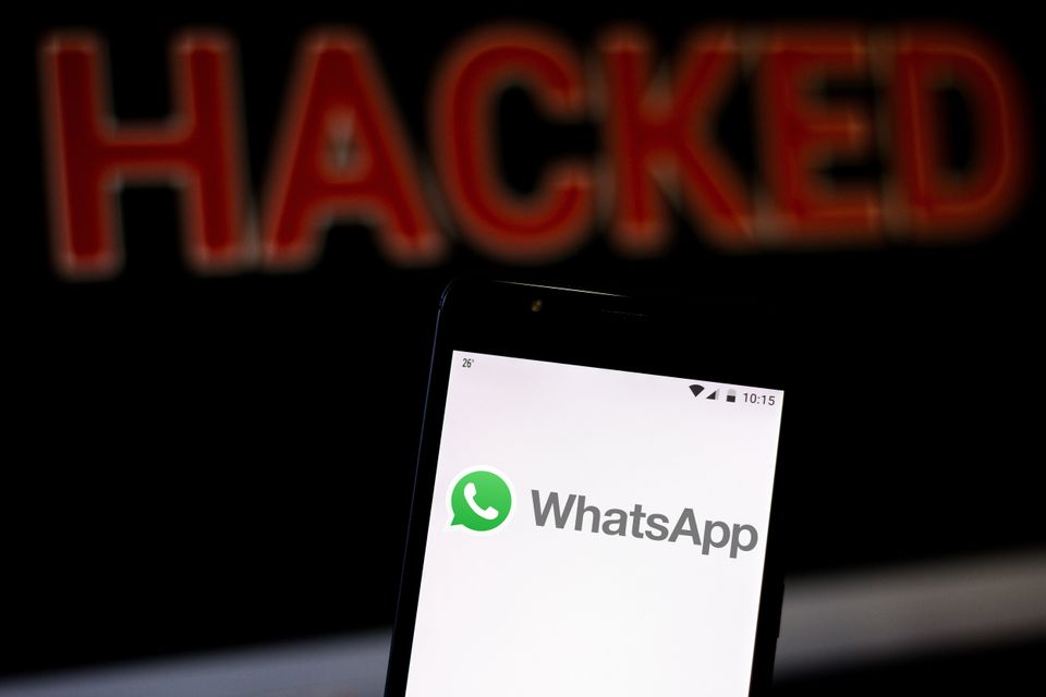 In this photo illustration, the WhatsApp logo is seen displayed on a smartphone and red alerting word...