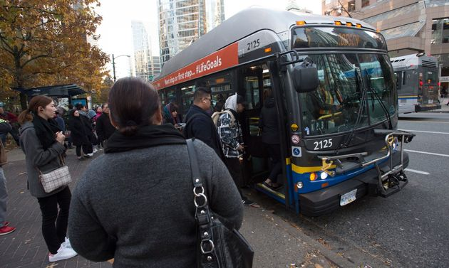 Passengers board a bus in downtown Vancouver, Friday, November, 1,